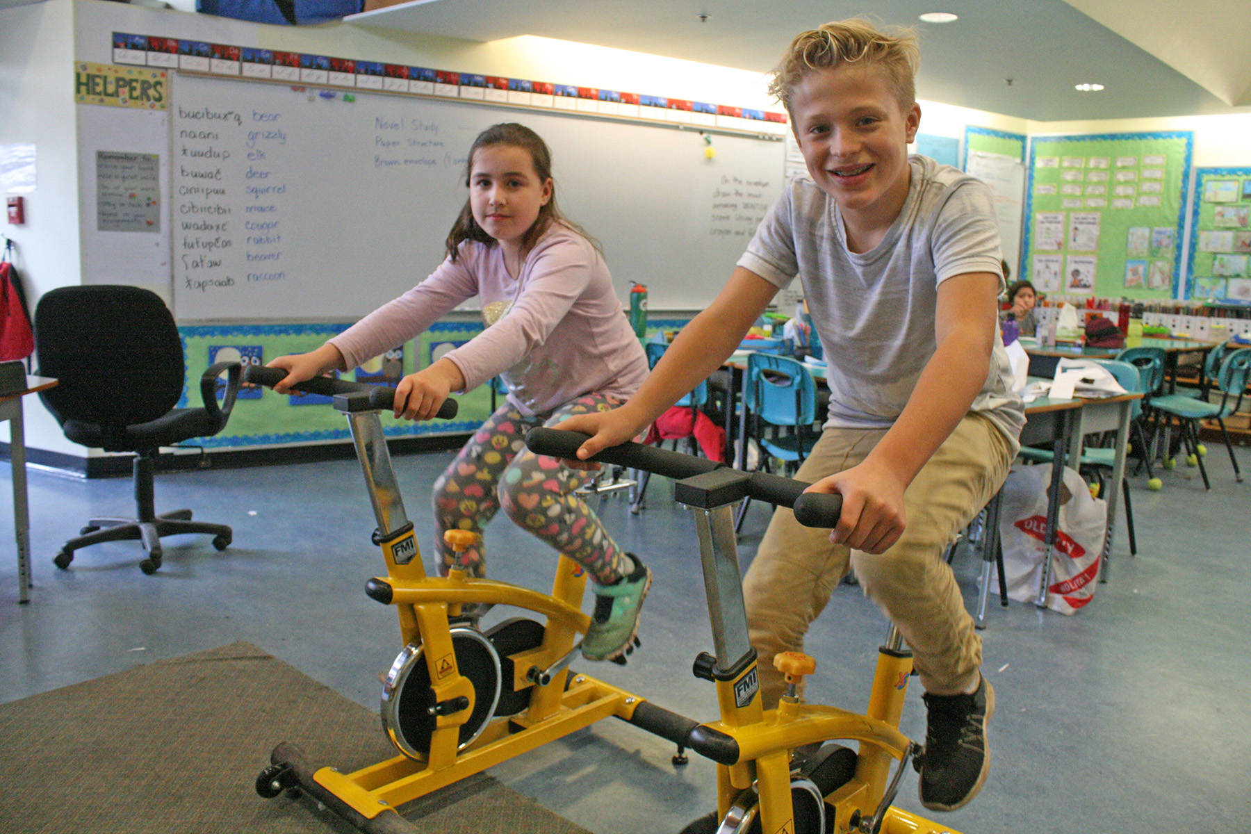 Students Brooklyn Buckingham and Gunnar Barlee use the bike trainer in their Strawberry Vale elementary classroom. The school will have one in each class for the new year. Travis Paterson/News Staff