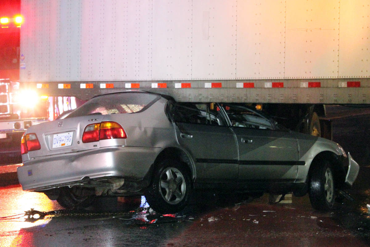 A Honda Civic was crushed underneath a semi-truck trailer following a collision on Departure Bay Road on Monday night. Nanaimo RCMP say the driver of the car fled the scene and has yet to be located. (Nicholas Pescod/NEWS BULLETIN)
