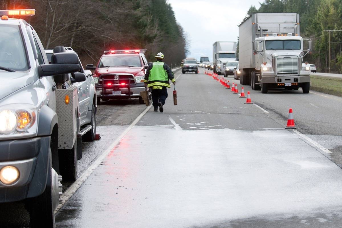 Traffic moves slowly on Highway 19 southbound near Parksville as Errington Volunteer Fire Department members mop up following a vehicle fire Sunday, Feb. 25, 2018. — J.R. Rardon photo