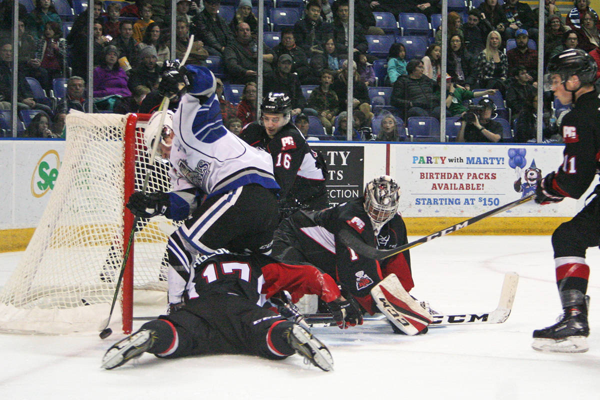 Victoria Royals captain Matthew Phillips (in white) and his teammates dropped a 2-1 overtime decision to Prince George last night and meet the Cougars in the Interior city again tonight. The single point in Western Hockey League action clinched a playoff berth for the Royals. Don Descoteau/Victoria News