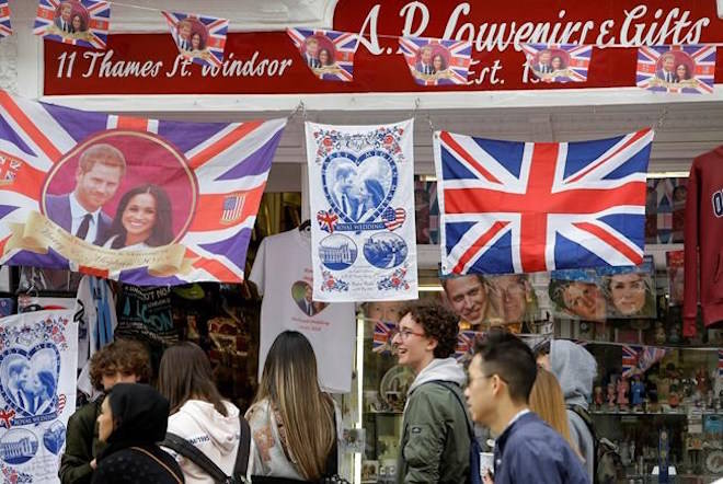 Royal memorabilia on sale near Windsor Castle in Windsor, England, Friday, May 11, 2018. All roads seem to lead to Windsor Castle, a magnificent fortress perched high on a hill topped by the royal standard when the queen is in residence. It is here, a favoured royal playground since William the Conqueror built the first structure here in 1070, that the royal wedding of Prince Harry and Meghan Markle will take place. (AP Photo/Alastair Grant)