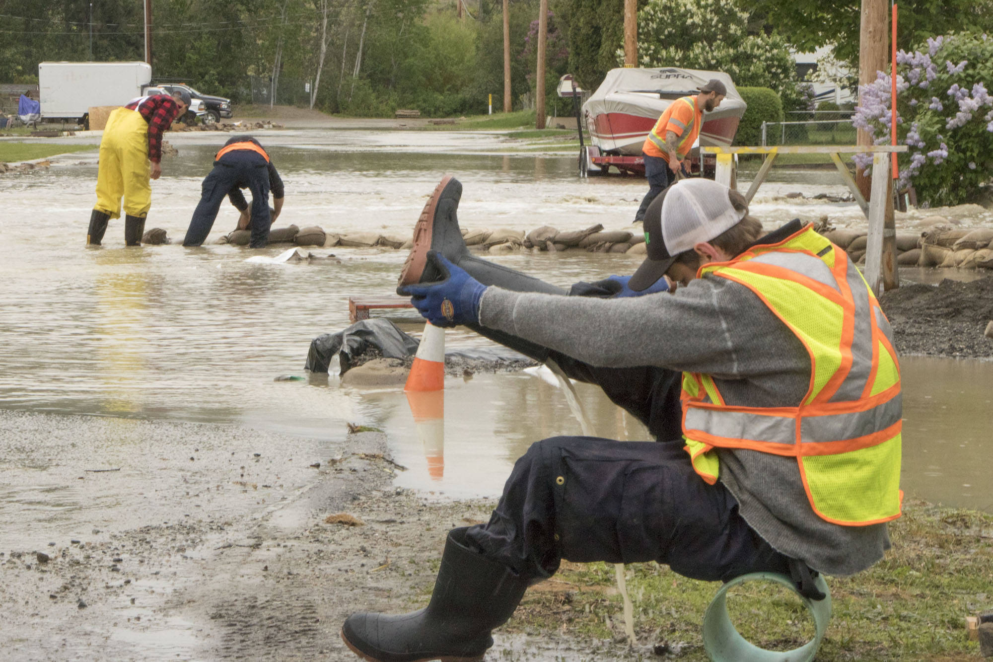 A man drains his boots before getting back to the sandbagging at 14th Avenue in Okanagan Falls. Even those with high boots on were not safe from the water, which reached a couple of feet in depth in places. Dustin Godfrey/Western News