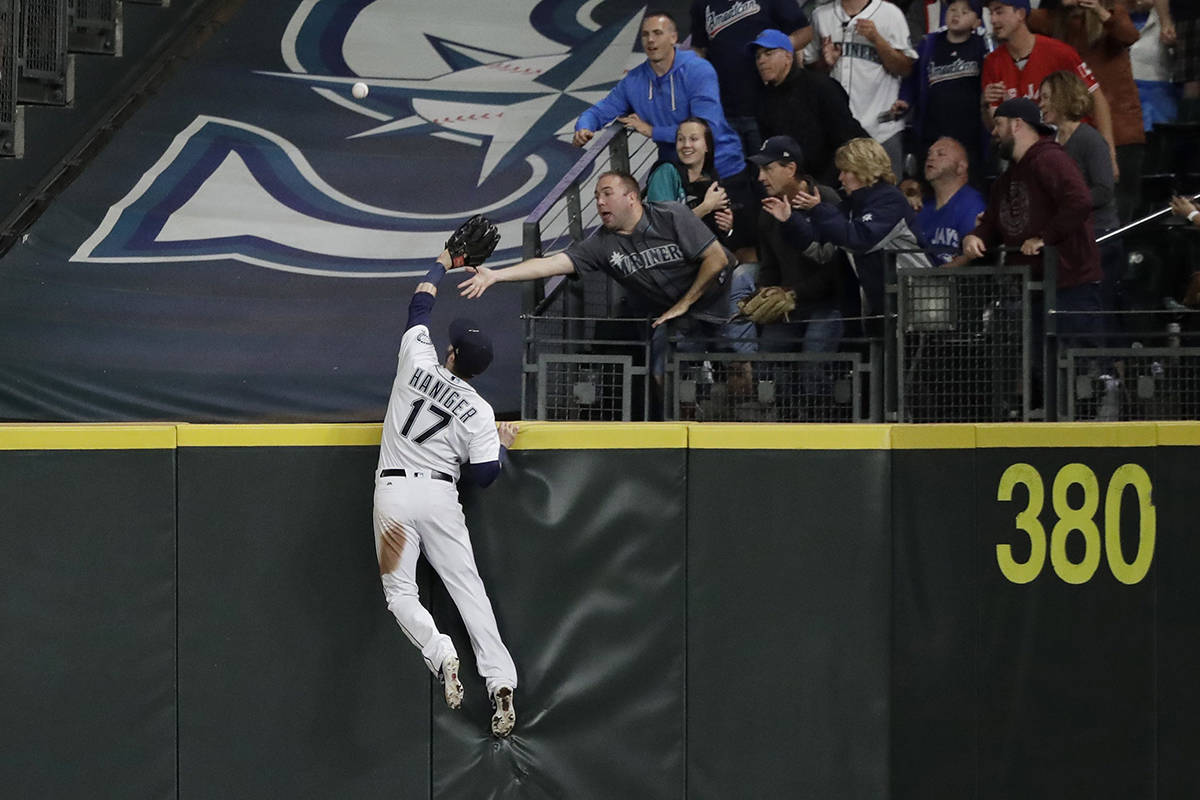Seattle Mariners right fielder Mitch Haniger leaps high at the wall but can't catch a two-run home run hit by Toronto Blue Jays' Kendrys Morales during the seventh inning of a baseball game, Thursday, Aug. 2, 2018, in Seattle. (AP Photo/Ted S. Warren)