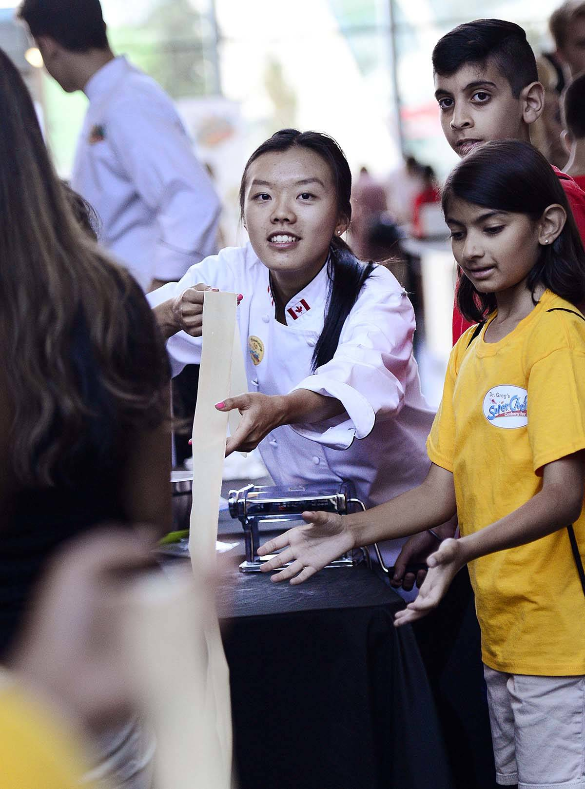 Cook Carissa Wong helps a group of kids make pasta for the long noodle contest during the SuperChefs 10th Anniversary event at City Hall in Surrey, British Columbia, on August 17, 2018. Ryan McLeod/Freelance