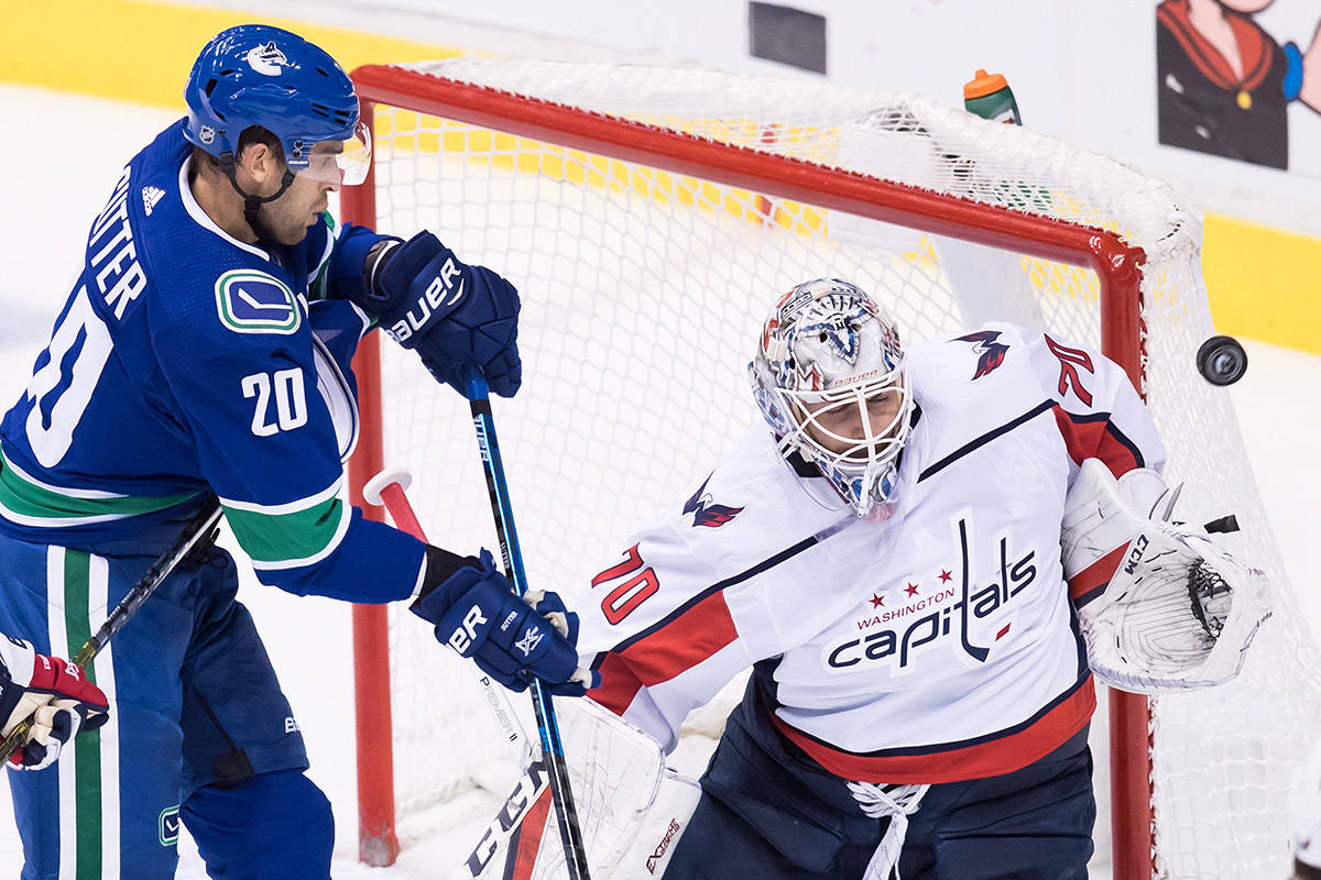 Washington Capitals goalie Braden Holtby (70) makes the save as Vancouver Canucks' Brandon Sutter (20) attempts to get his stick on the puck during the second period of an NHL hockey game in Vancouver, on Monday October 22, 2018. THE CANADIAN PRESS/Darryl Dyck