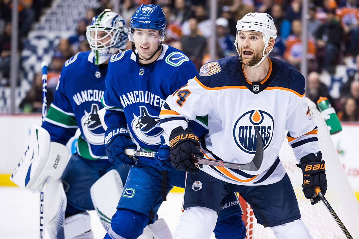 Edmonton Oilers' Zack Kassian, right, holds Vancouver Canucks' Ben Hutton's stick as they battle for position in front of Vancouver goalie Jacob Markstrom, back left, of Sweden, during first period NHL hockey action in Vancouver on Sunday, Dec. 16, 2018. THE CANADIAN PRESS/Darryl Dyck
