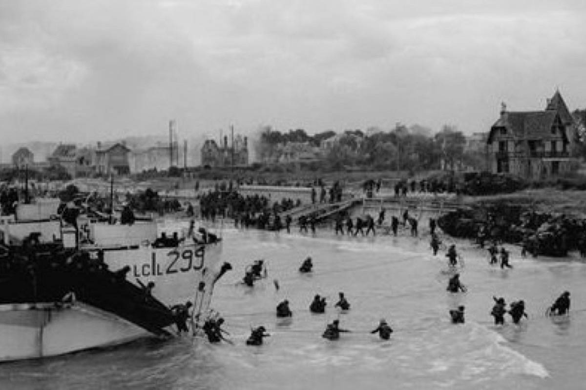 View looking east along 'Nan White' Beach, showing personnel of the 9th Canadian Infantry Brigade landing from LCI(L) 299 of the 2nd Canadian (262nd RN) Flotilla on D-Day. (CP PHOTO) 1998 (National Archives of Canada-Gilbert Alexandre Milne) PA-137013