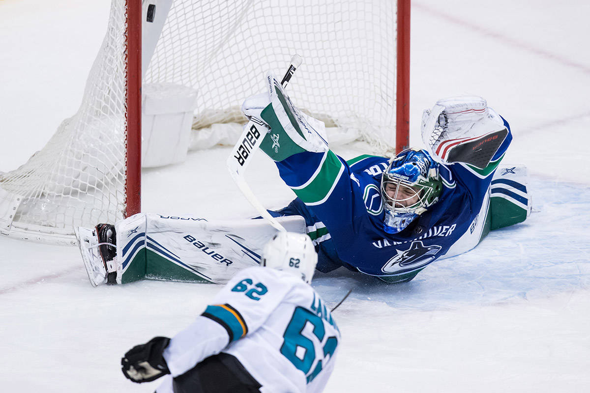 San Jose Sharks' Kevin Labanc, bottom, scores against Vancouver Canucks goalie Michael DiPietro during the second period of an NHL hockey game in Vancouver, on Monday February 11, 2019. THE CANADIAN PRESS/Darryl Dyck