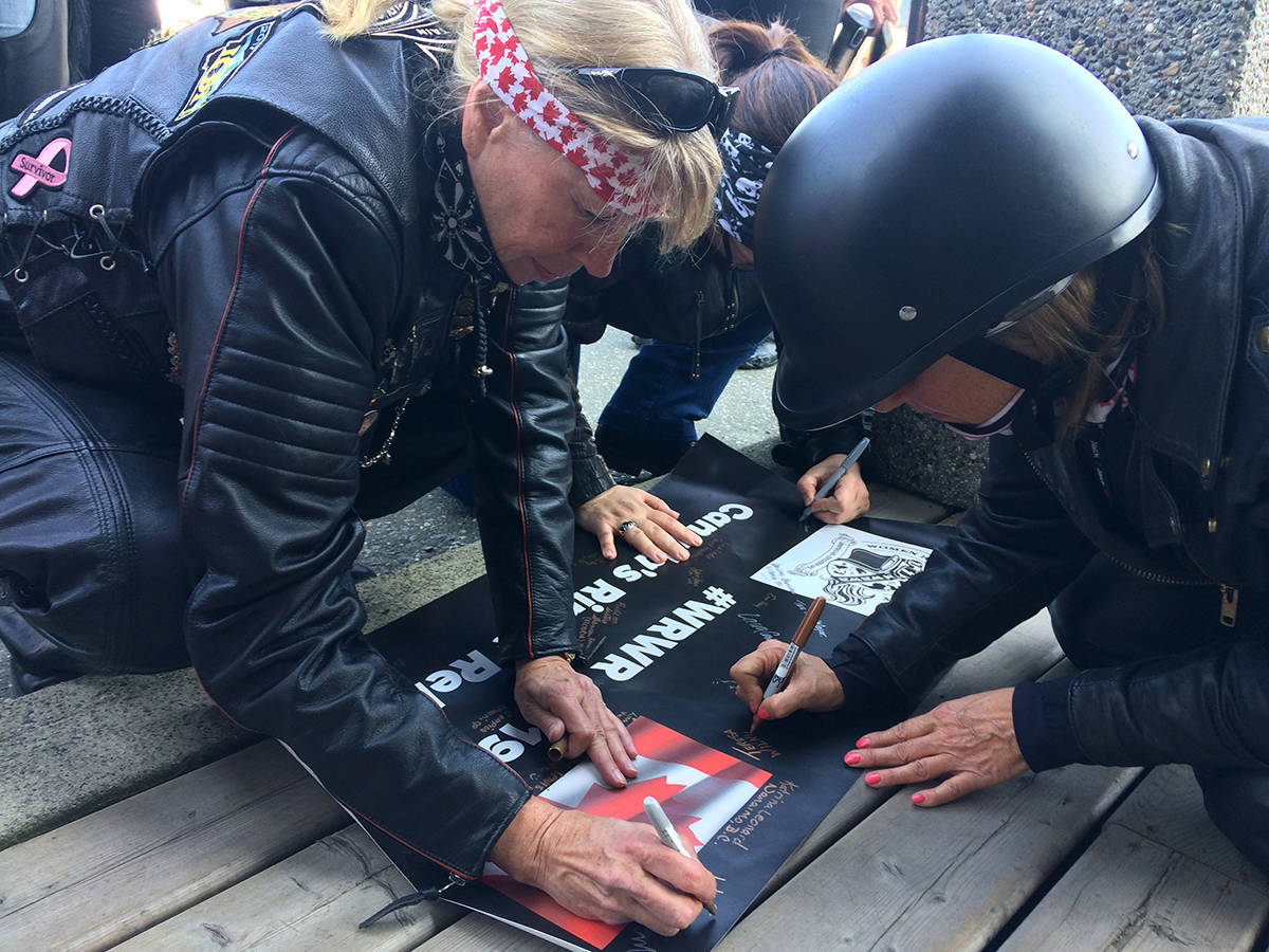 Women riders sign a banner for a leg of a Ripple Rally from Victoria to Balfour. They stopped in Chilliwack on May 31 for a leg to Kelowna. (Jessica Peters/ The Progress)