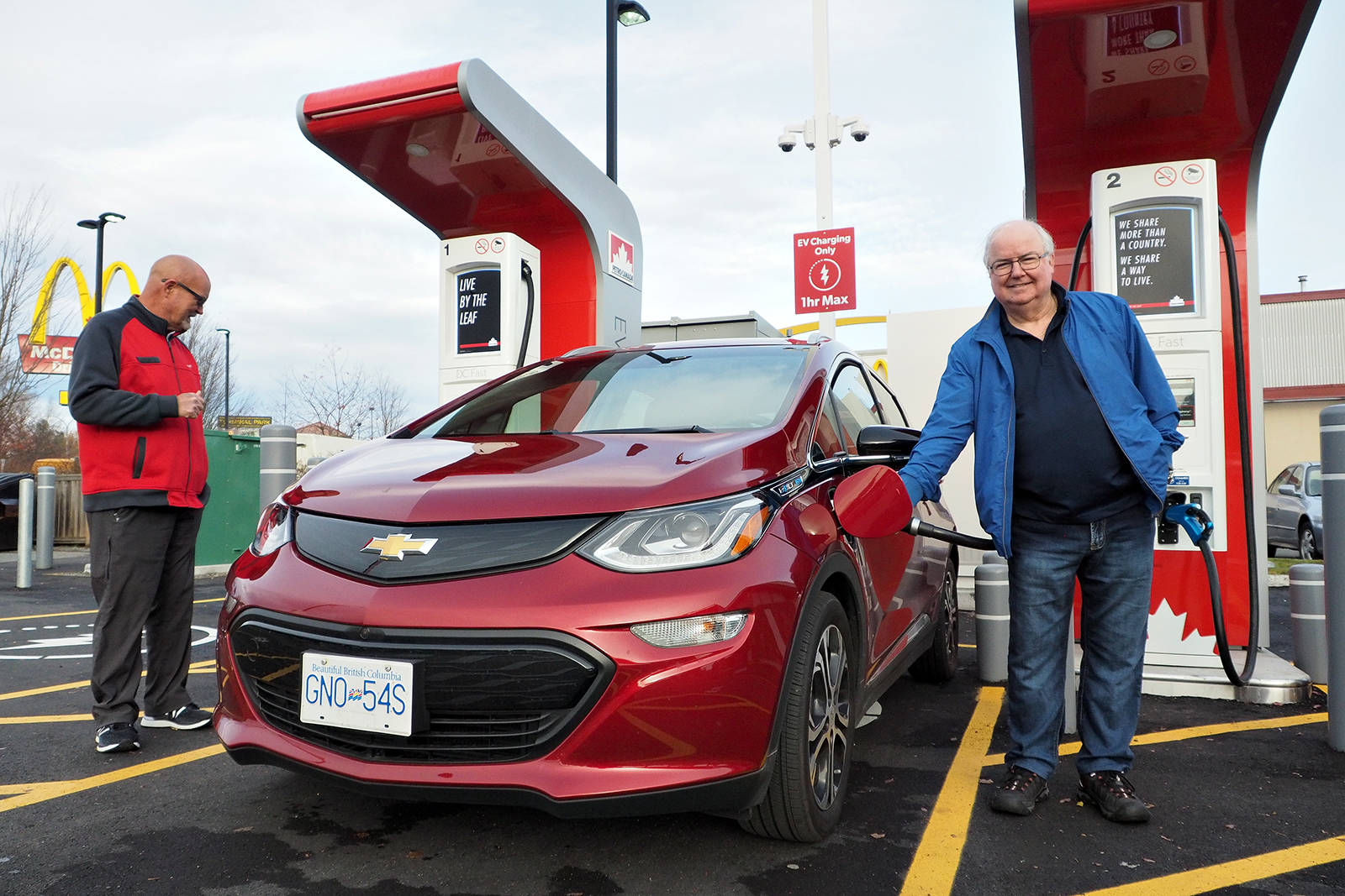 Ed Tkachuk, Nanaimo Petro-Canada station franchise owner, left, checks vehicle clearances from bulwarks installed to protect charging stations, as customer Richard McFadyen tops up the charge on his Chevy Bolt electric car for a trip to the Lower Mainland. CHRIS BUSH/The News Bulletin