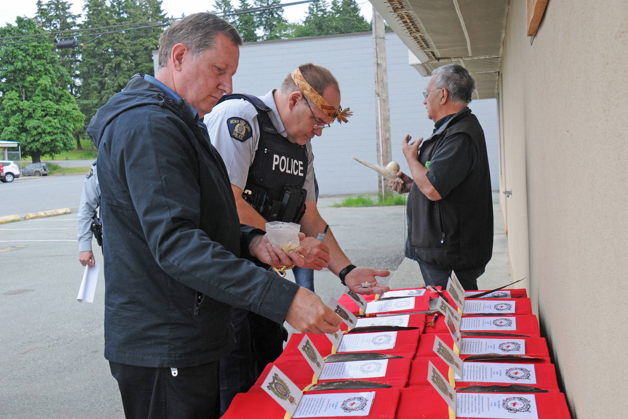 Port Alberni RCMP Acting Officer in Charge Sgt. Peter Dionne, left, sprinkles powdered Devil's Club over the eagle feather folders while RCMP Cst. Pete Batt follows with a candle flame during a blessing ceremony outside the Nuu-chah-nulth Quu?asa Program building on Third Avenue, Friday, June 5, 2020. Quu?asa cultural worker Joseph Tom, right, waits to say a prayer over the folders. (SUSAN QUINN/ Alberni Valley News)