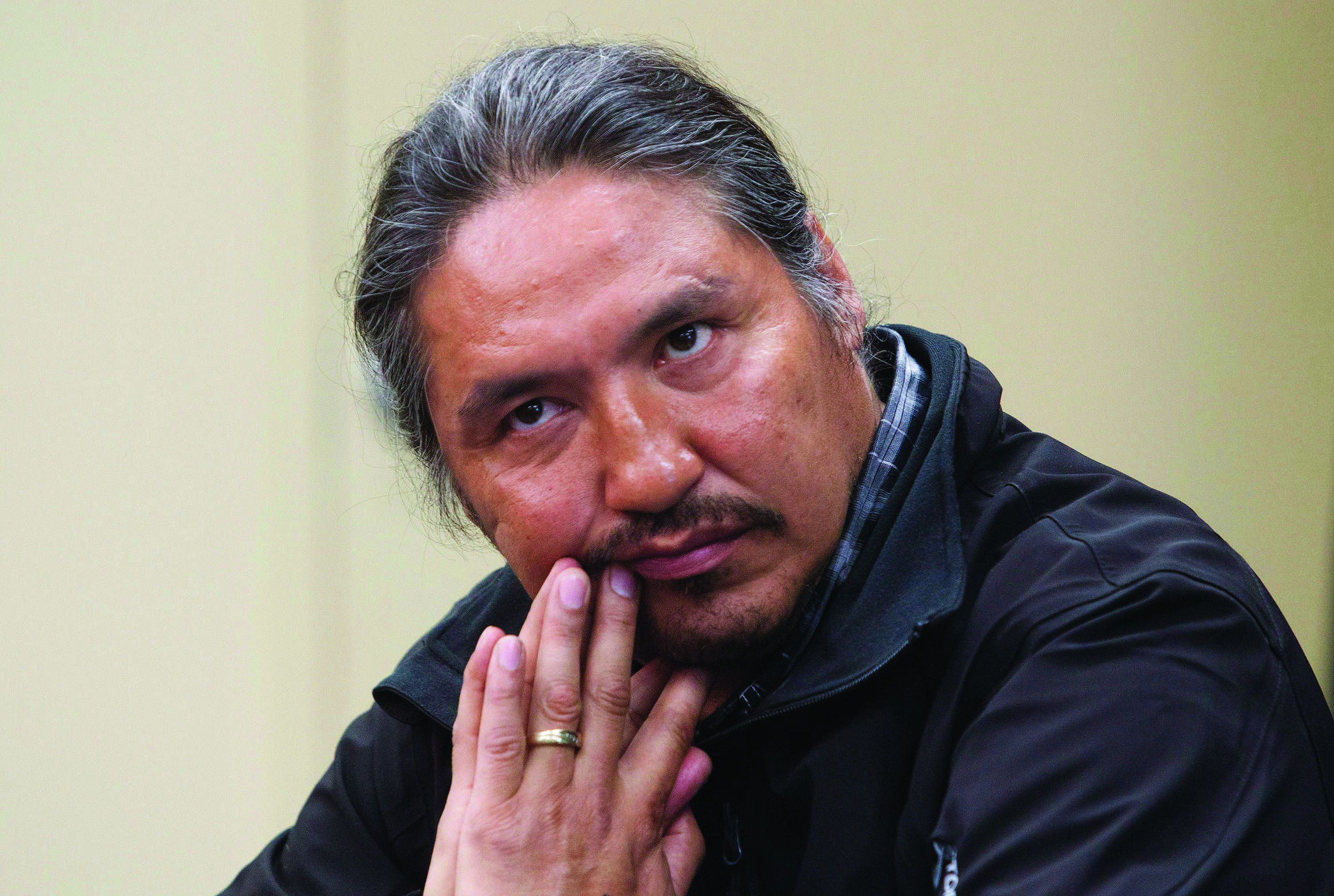 """Chief Allan Adam of the Athabasca Chipewyan First Nation listens as Archbishop Desmond Tutu speaks during a press conference in Fort McMurray, Alta. on Friday May 30, 2014. Adam says ongoing concerns about coerced sterilization of Indigenous women is nothing short of a """"crisis"""" and he wants to see a public inquiry into the allegations. THE CANADIAN PRESS/Jason Franson"""