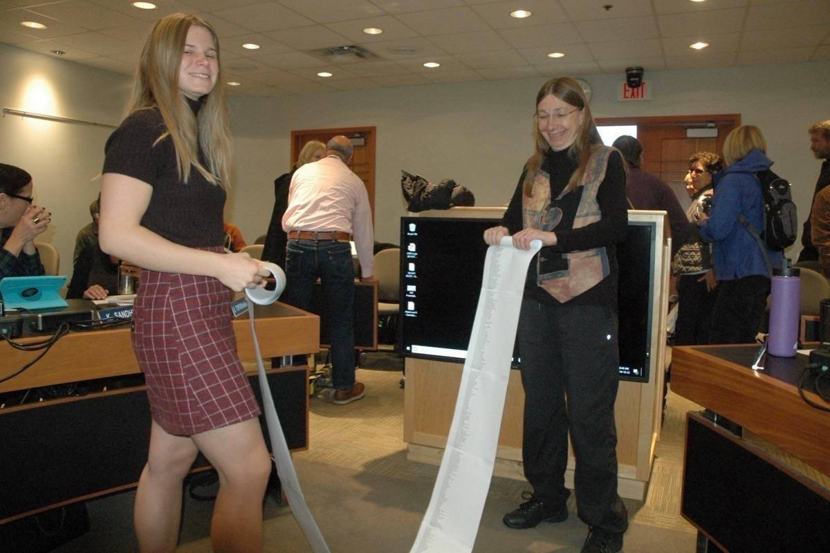 Katia Bannister, left, from the Cowichan chapter of the Earth Guardians, and Jane Kilthei from One Cowichan role up a petition with more than 1,800 names asking the CVRD to declare a climate emergency at a meeting last year. (File photo)