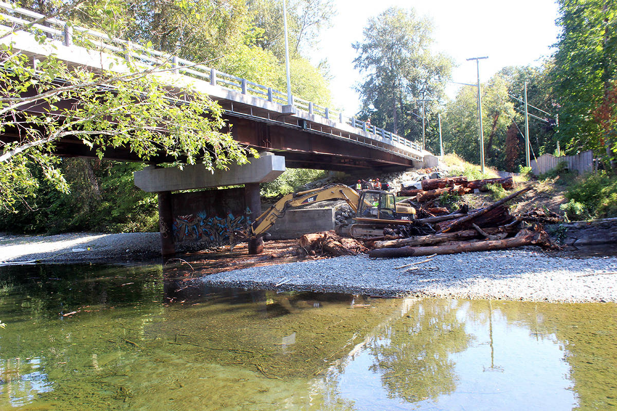 North Cowichan crews work to clear log debris under the Chemainus River bridge on Chemainus Road. (Photo by Don Bodger)