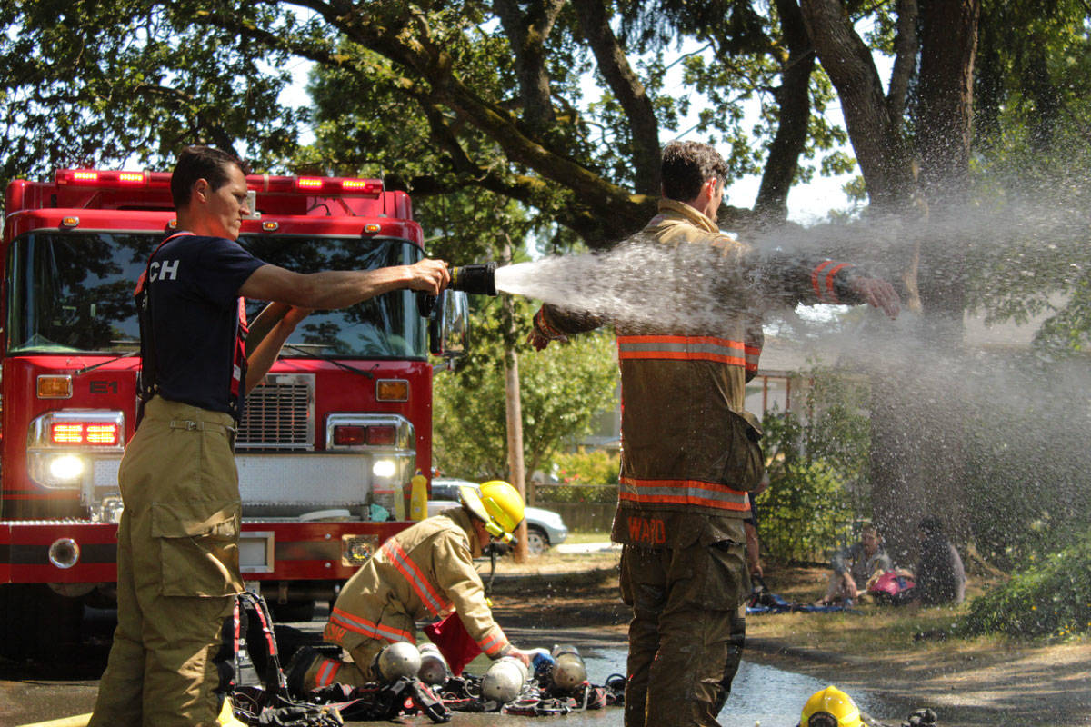 Firefighter Joel Anthony (left) helps fellow Saanich firefighter Josh Ward spray down his gear after extinguishing a house fire in the 500-block of Walter Avenue. (Devon Bidal/News Staff)