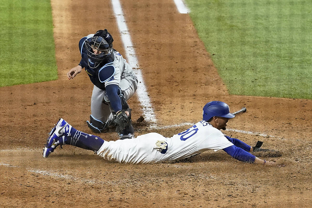 Los Angeles Dodgers' Mookie Betts scores past Tampa Bay Rays catcher Mike Zunino during the sixth inning in Game 6 of the baseball World Series Tuesday, Oct. 27, 2020, in Arlington, Texas. (AP Photo/David J. Phillip)