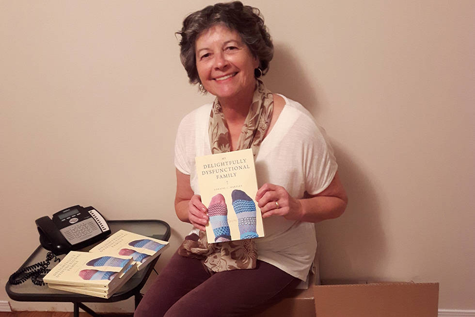 "Comox author Loraine Hartley, with a few copies of her debut novel, ""My Delightfully Dysfunctional Family."" Photo supplied"