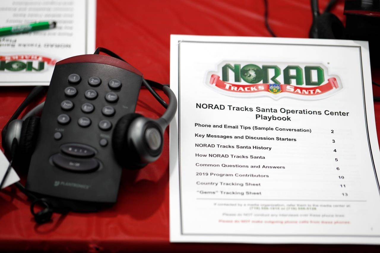 FILE - In this Dec. 23, 2019, file photo a playbook sits next to a telephone set up in the NORAD Tracks Santa center at Peterson Air Force Base in Colorado Springs, Colo. The North American Aerospace Defense Command has announced that NORAD will track Santa on December 24, just as it has done for 65 years. But there will be some changes: Not every child will be able to get through to a volunteer at NORAD's call center to check on Santa's whereabouts, as they have in years before. (AP Photo/David Zalubowski, File)