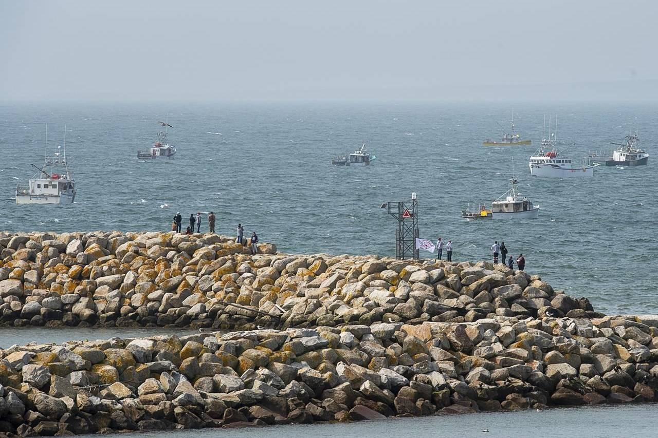 Members of the Sipekne'katik First Nation, supported by other First Nations, stand on the breakwater in Saulnierville, N.S., as non-indigenous boats protest the launch the Mi'kmaq self-regulated fishery on Thursday, Sept. 17, 2020. THE CANADIAN PRESS/Andrew Vaughan