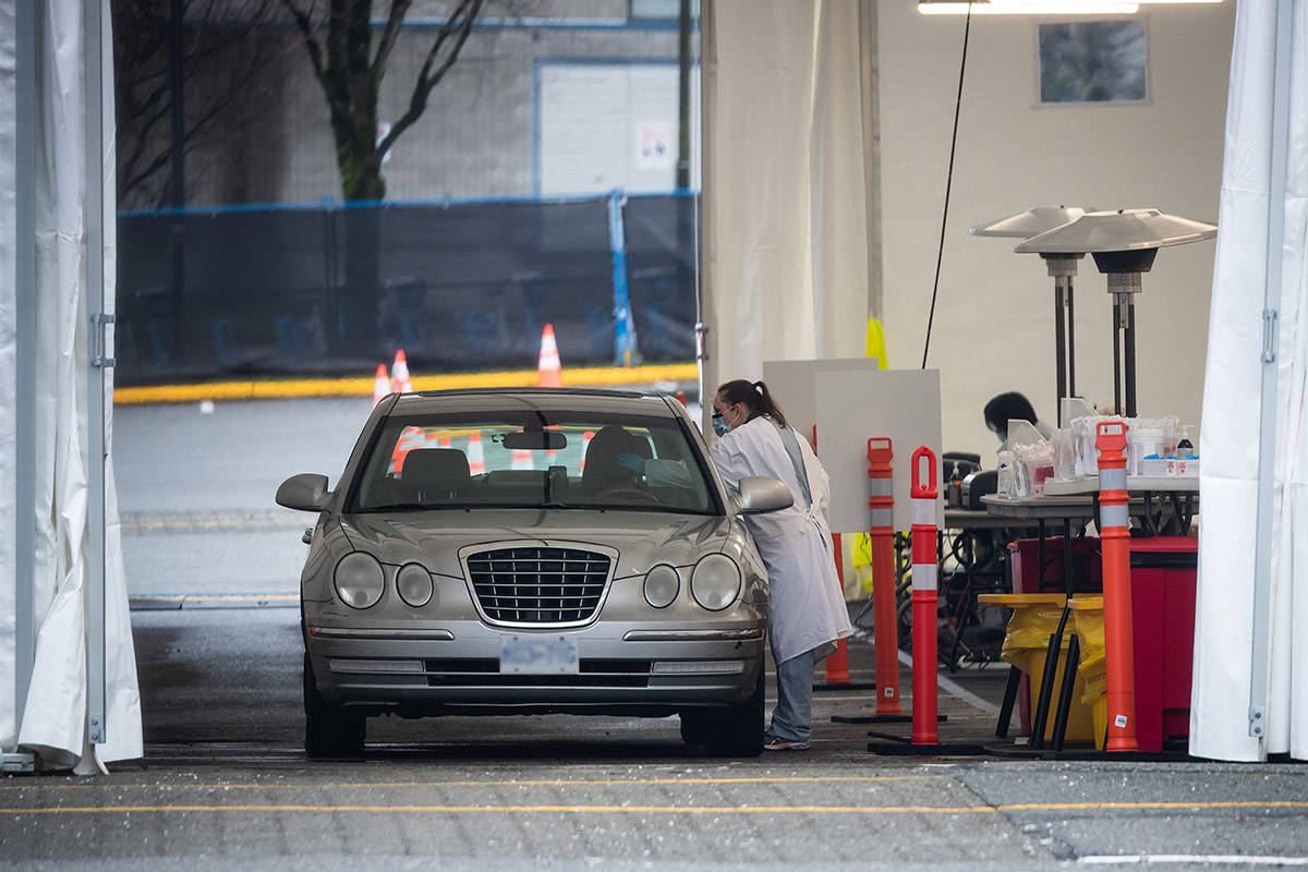 A healthcare worker takes a swab from a driver at a drive-thru COVID-19 testing facility, in Vancouver, on Monday, December 28, 2020. THE CANADIAN PRESS/Darryl Dyck