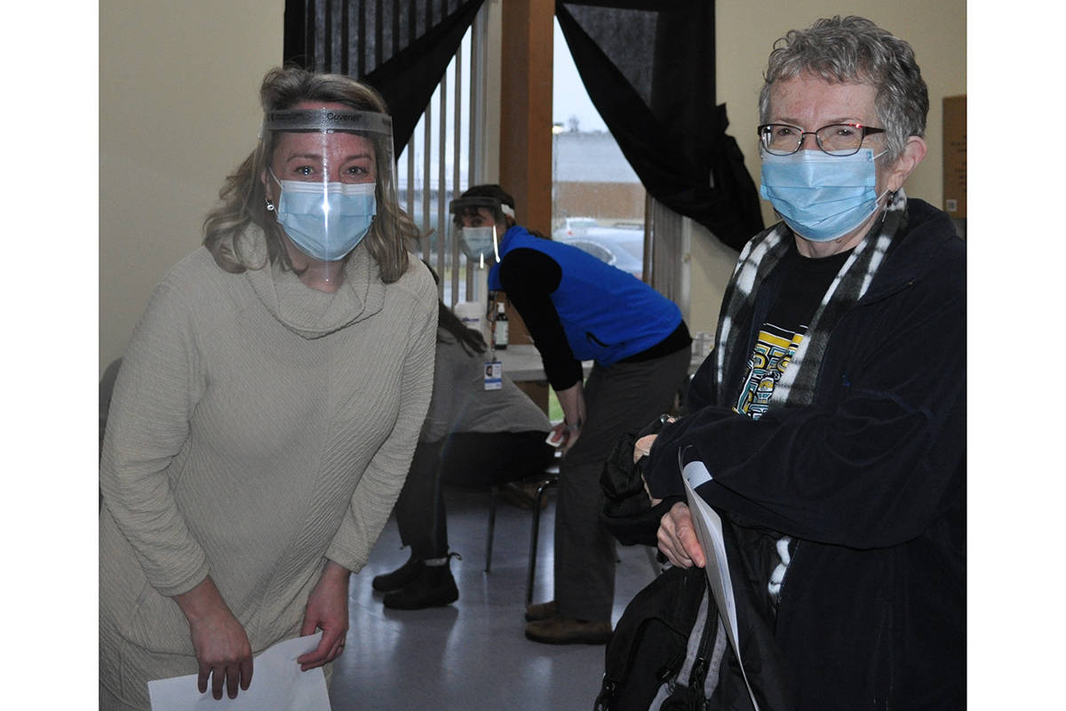 'Namgis Community Health Nurse Nicole James (left) smiling with Mary Cook (right) who received the first COVID-19 vaccine on Alert Bay on Jan. 5. (Gina Wadhams photo)