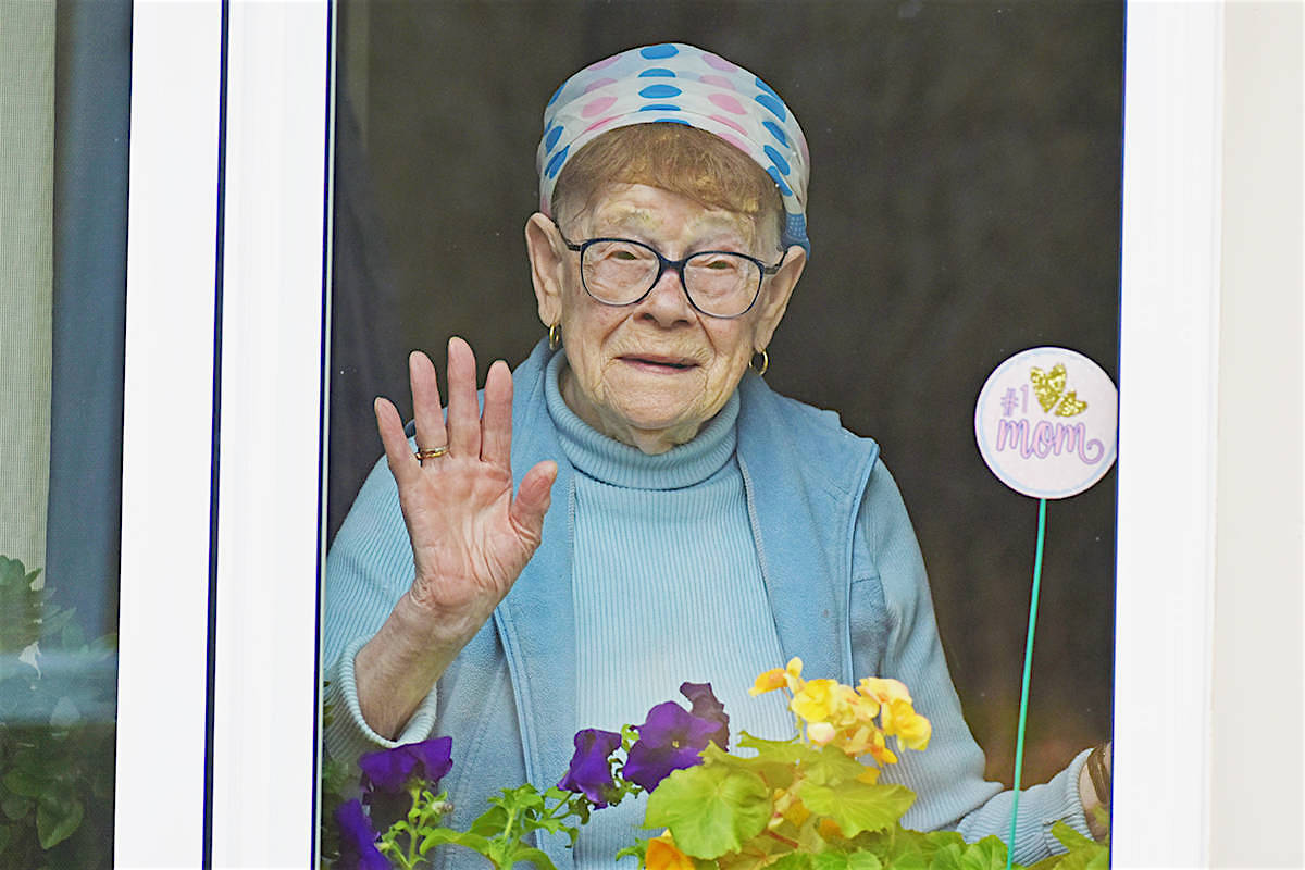 Rose Sawka, 91, waves to her son through the window of a care home in Prince Rupert in October. Residents of the care home received their first vaccine dose Jan. 20. (K-J Millar/The Northern View)