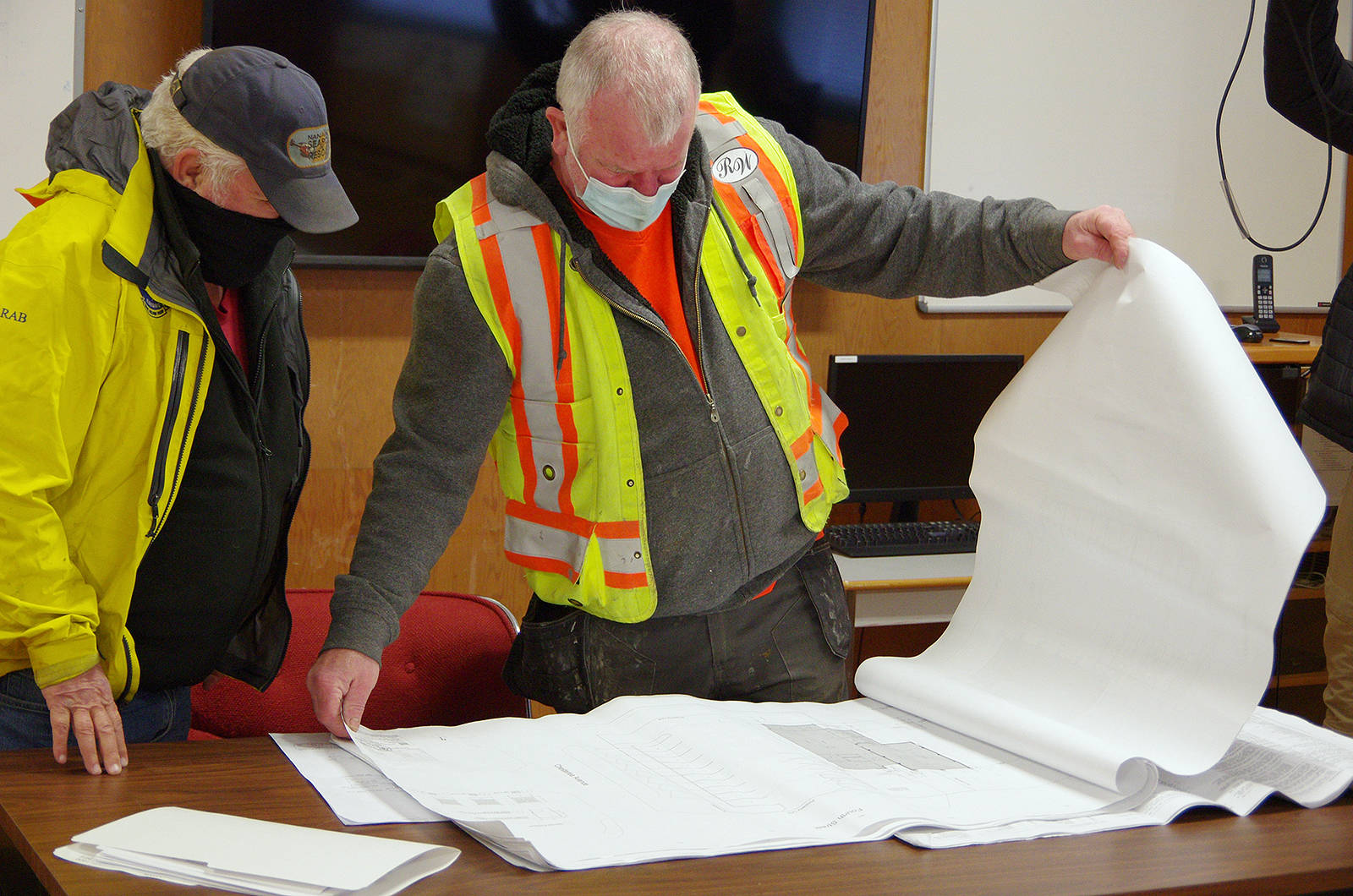 Kevin McNeill, Nanaimo Search and Rescue past president, left, looks over architectural drawings with Darren McKenna, site superintendent with construction contractor R.W. (Bob) Wall, for renovations to NSAR's headquarters that got underway Tuesday, Jan. 26. (Chris Bush/News Bulletin)
