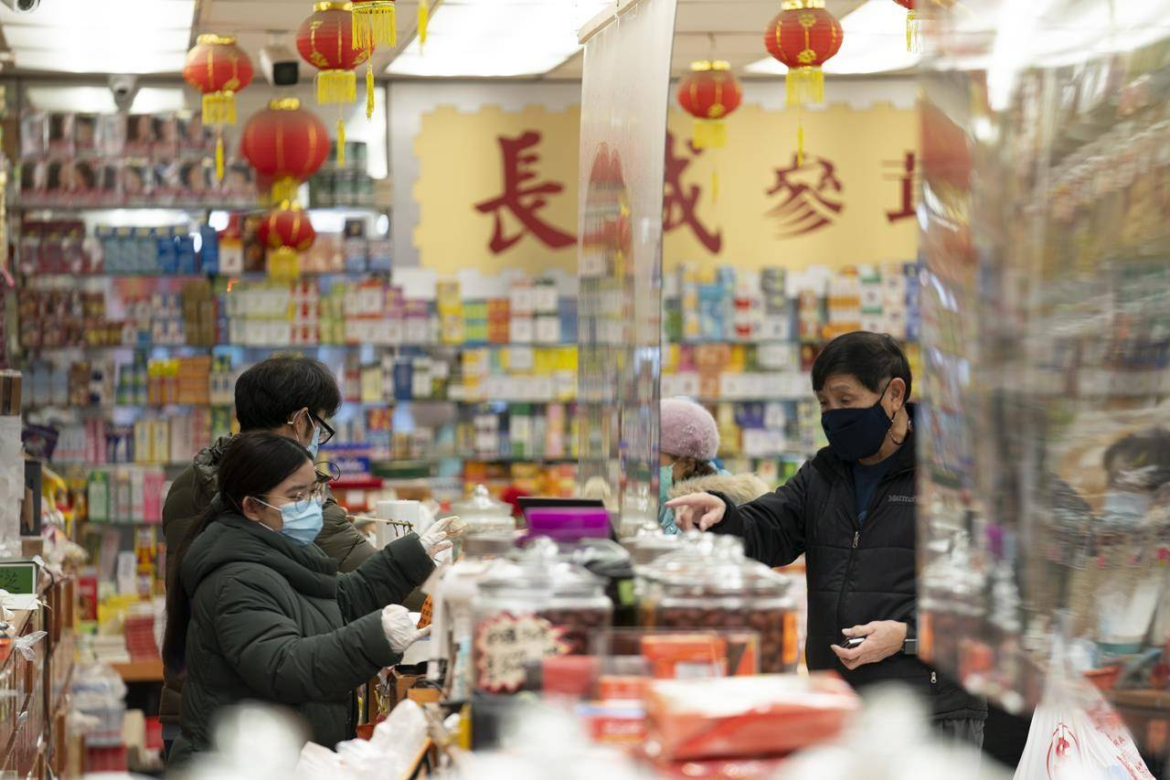 People shop in Chinatown in Vancouver, Friday, February 5, 2021. COVID-19 has taken a toll on many Canadians, but for Chinese-Canadians the impacts have been magnified by racism aimed at individuals and businesses, community leaders say. THE CANADIAN PRESS/Jonathan Hayward