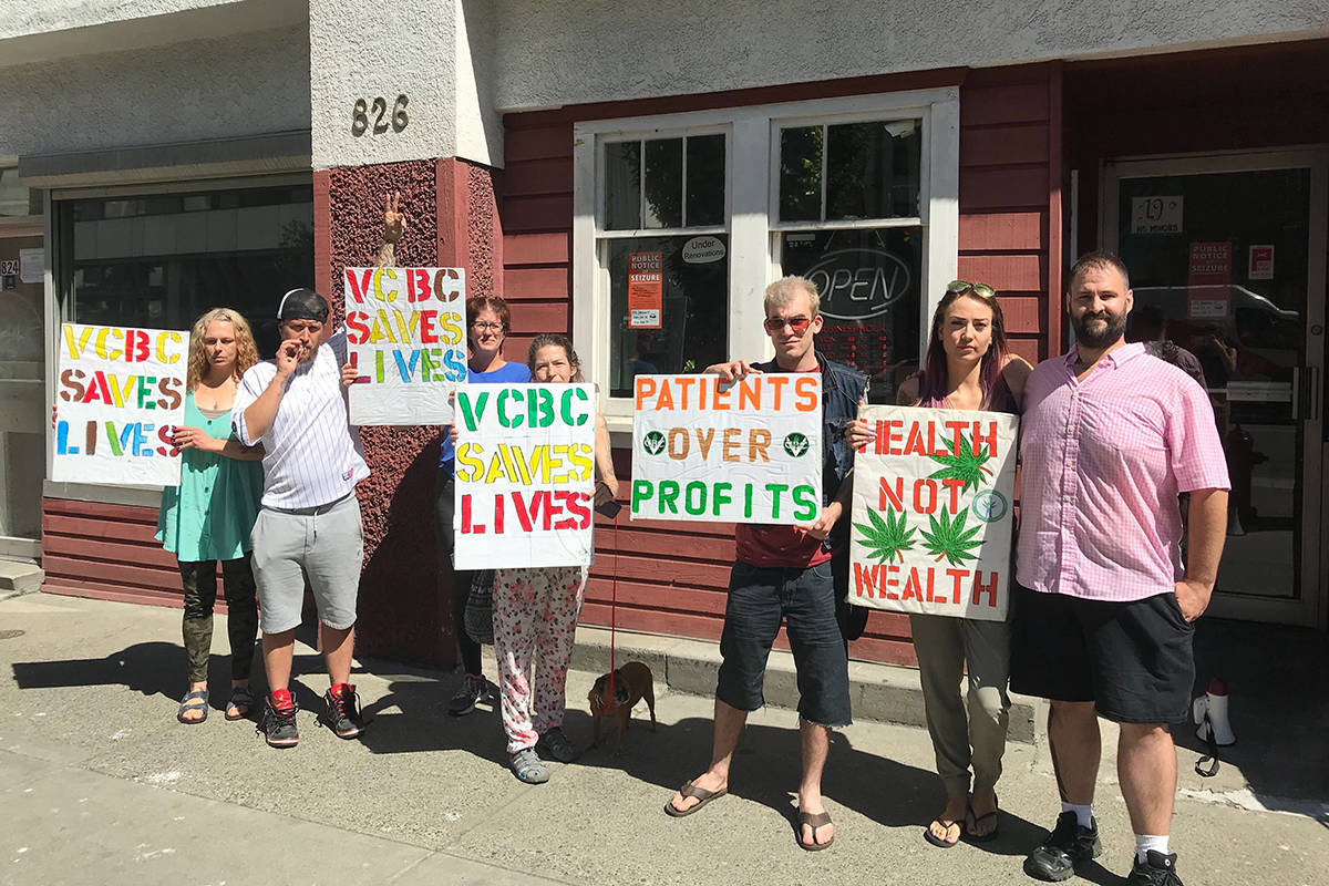 Members and supporters of the Victoria Cannabis Buyers Club stand outside the Johnson Street location protesting a police raid. (Black Press Media file photo)