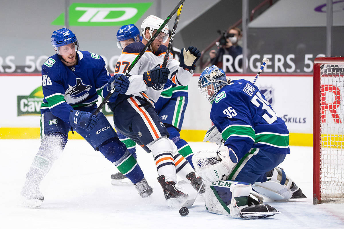 Vancouver Canucks goalie Thatcher Demko (35) stops Edmonton Oilers' Connor McDavid (97) as Vancouver's Nate Schmidt (88) defends during the first period of an NHL hockey game in Vancouver, on Saturday, March 13, 2021. THE CANADIAN PRESS/Darryl Dyck