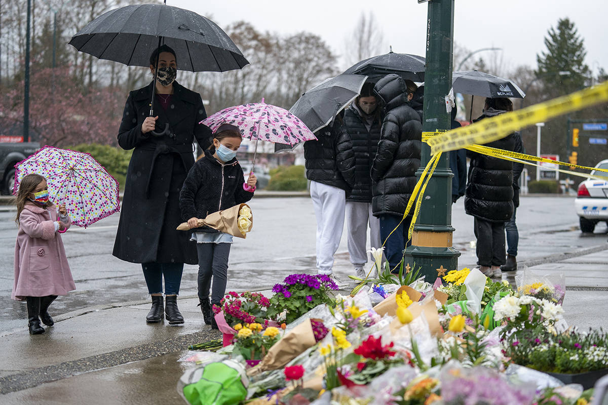 People lay flowers at a makeshift memorial outside of the Lynn Valley Library in North Vancouver, B.C., Sunday, March 28, 2021. The memorial is for stabbing victims that were attacked by a man with a knife on Saturday, sending several to hospital and leaving one dead. THE CANADIAN PRESS/Jonathan Hayward