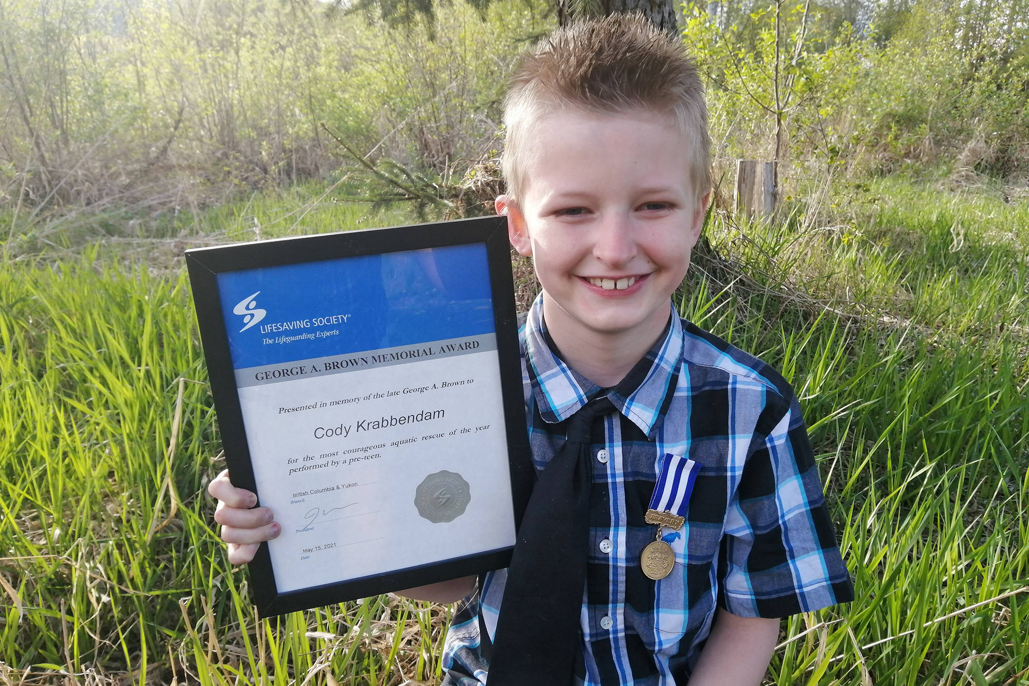 Ranchero resident Cody Krabbendam proudly displays the Lifesaving Society awards he recently received for a rescuing another boy while swimming at Sicamous Beach in July 2020. (Contributed)