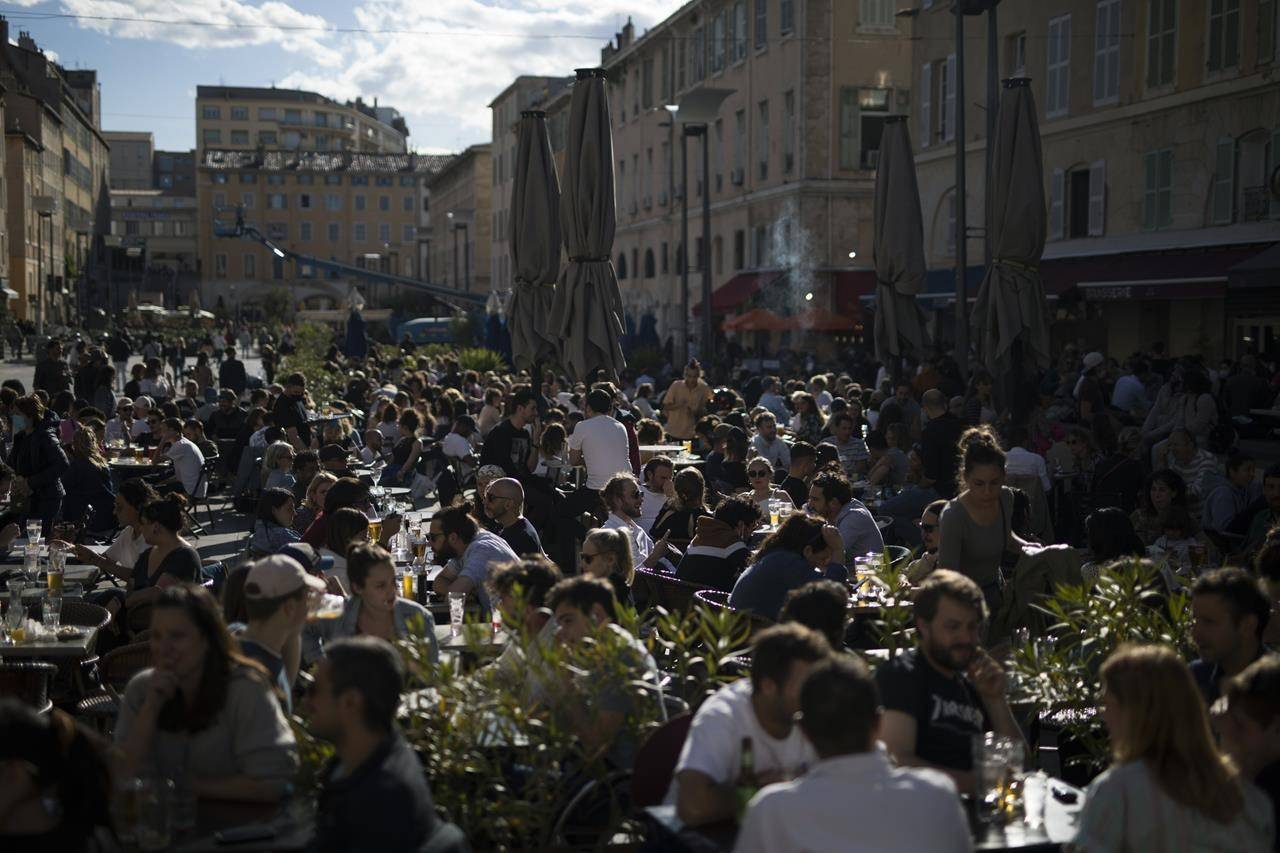 People drink outdoors on bar terraces in Marseille southern France, Wednesday, May 19, 2021. Cafe and restaurant terraces reopened Wednesday after a pandemic shutdown of more than six months deprived people of what feels like the essence of life in France. (AP Photo/Daniel Cole)