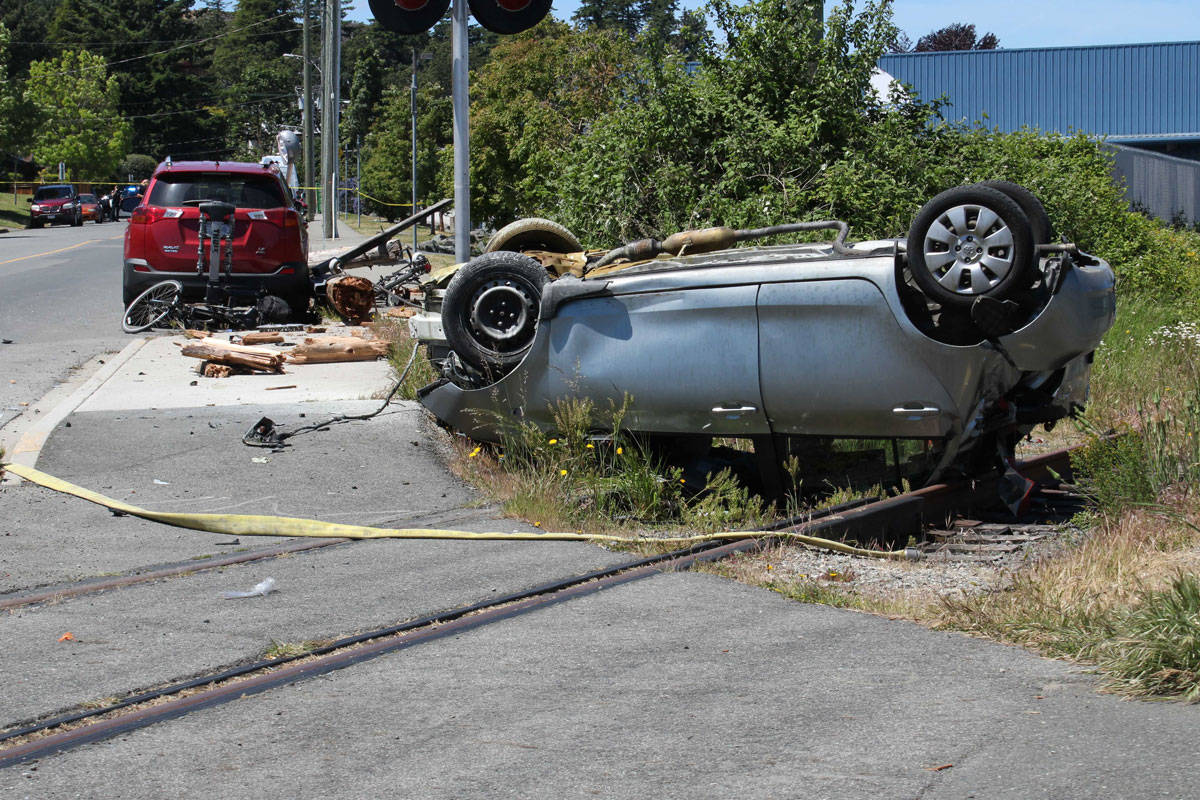 Bystanders rescued a driver from a flaming car after rollover crash in Esquimalt on May 29. (Jake Romphf/News Staff)