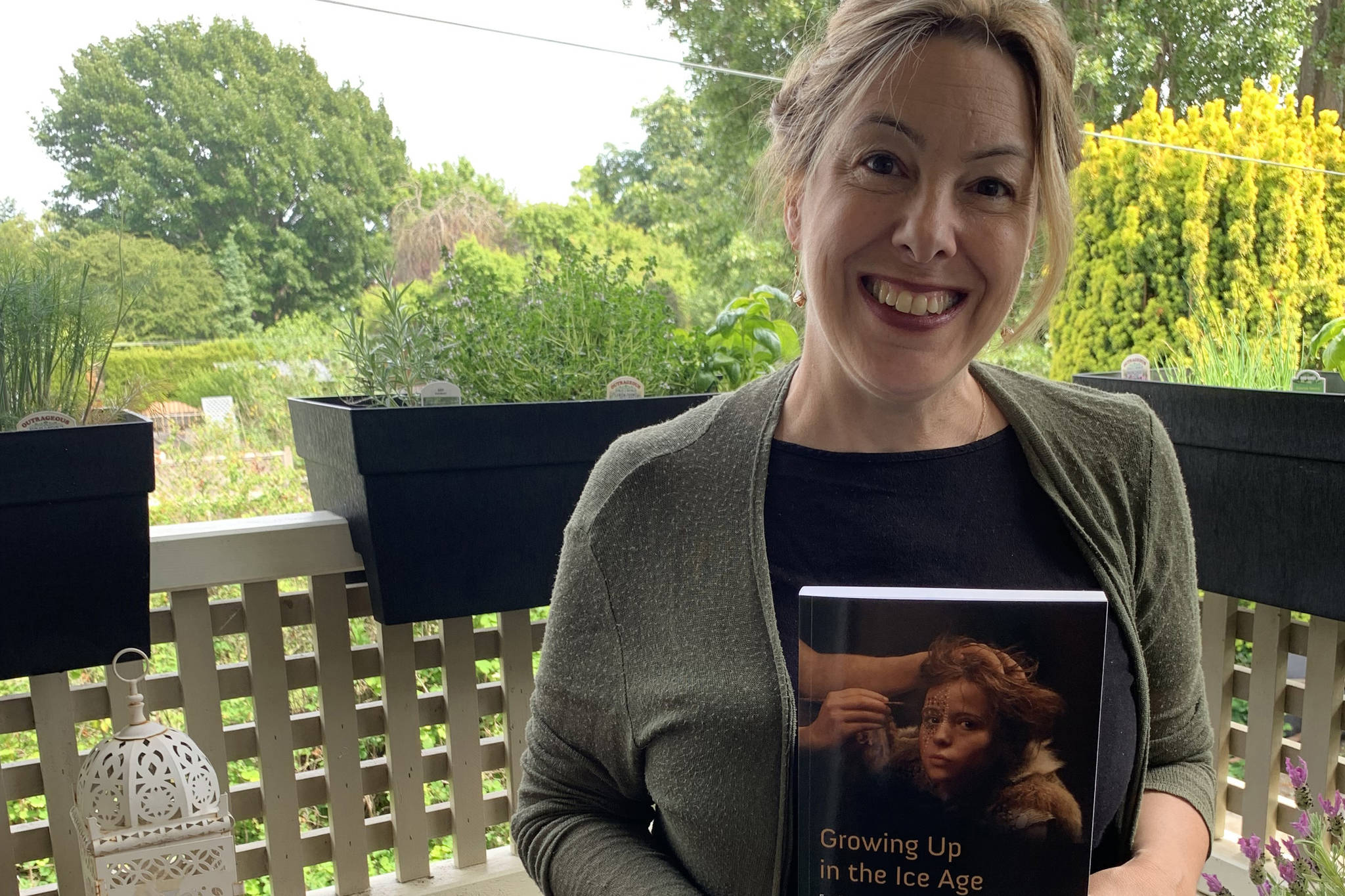 UVic Department of Anthropology chair and professor, April Nowell, at home with a copy of her new book, Growing Up In the Ice Age. (Courtesy of April Nowell)