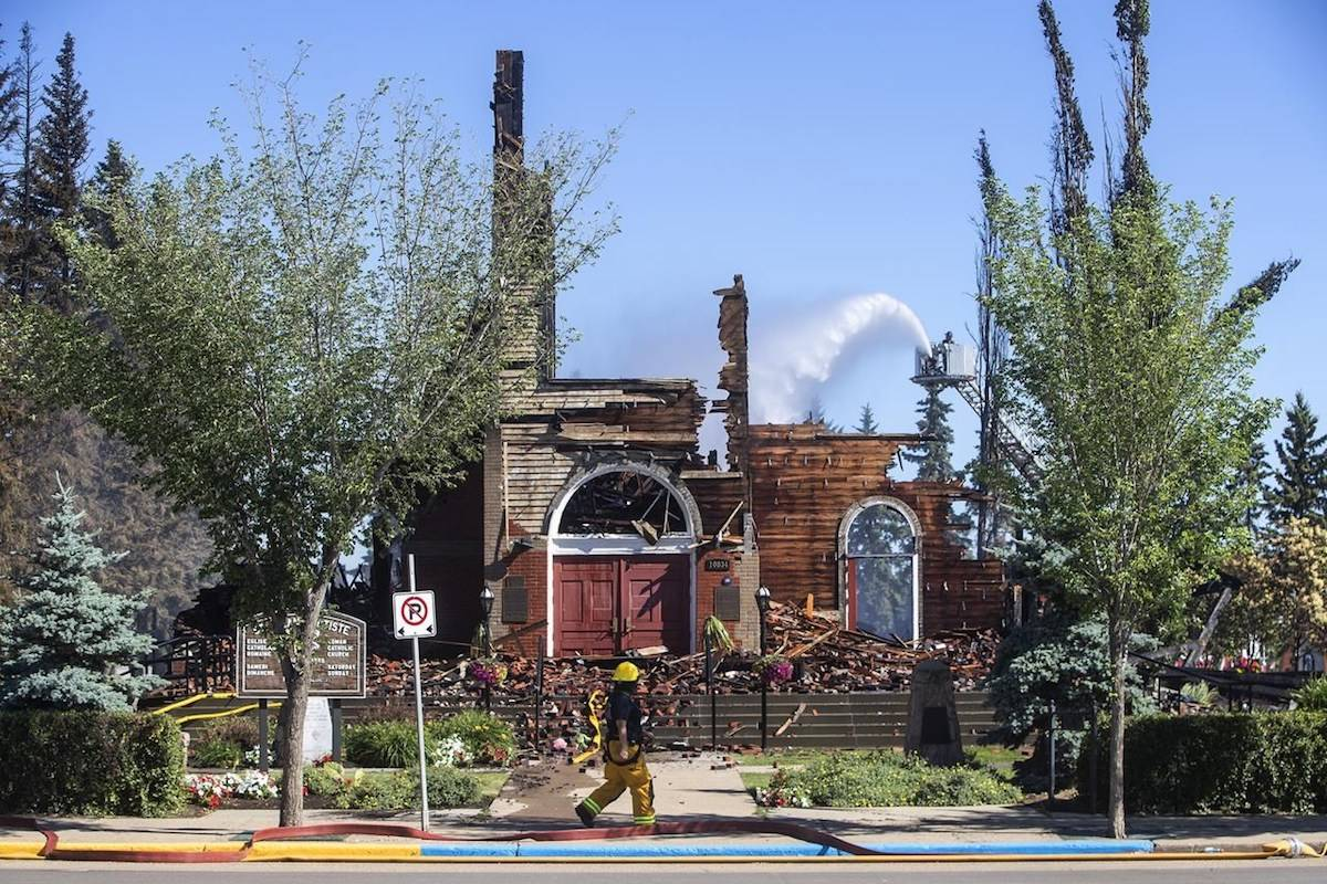 St. John Baptiste Parish Catholic church is shown in Morinville Alta, on Wednesday, June 30, 2021 as firefighters put out hot spots. RCMP are calling the fire suspicious. THE CANADIAN PRESS/Jason Franson