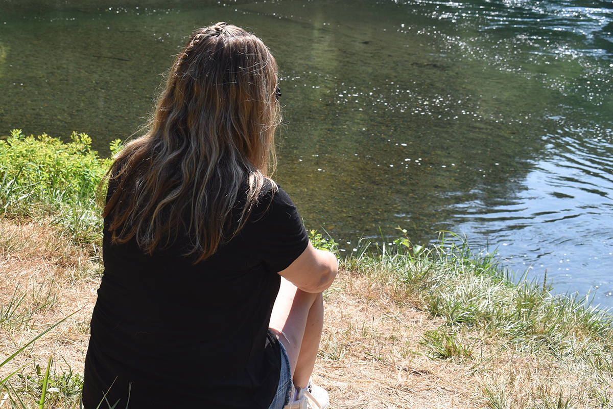 """Cameron Thompson's aunt, Brenda Payne, looks into the Puntledge River at the location where Cameron dove in for a swim. """"This was just a shallow dive, to go for a swim, and he misjudged."""" Cameron Thompson remains in hospital in Vancouver with a spinal injury. Photo by Terry Farrell"""