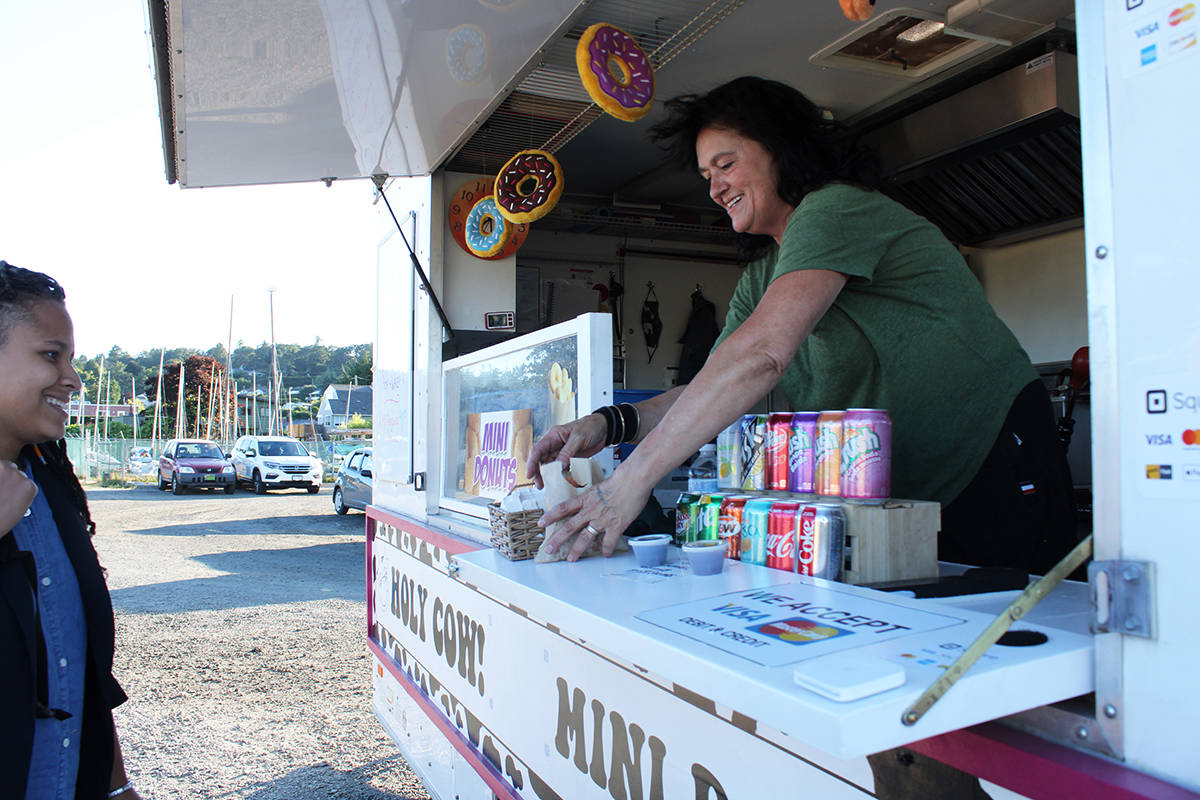 Tracey Godfrey serves her last customer of the day from the Holy Cow Mini Donuts food truck, parked at Cadboro-Gyro Park. (Jake Romphf/News Staff)