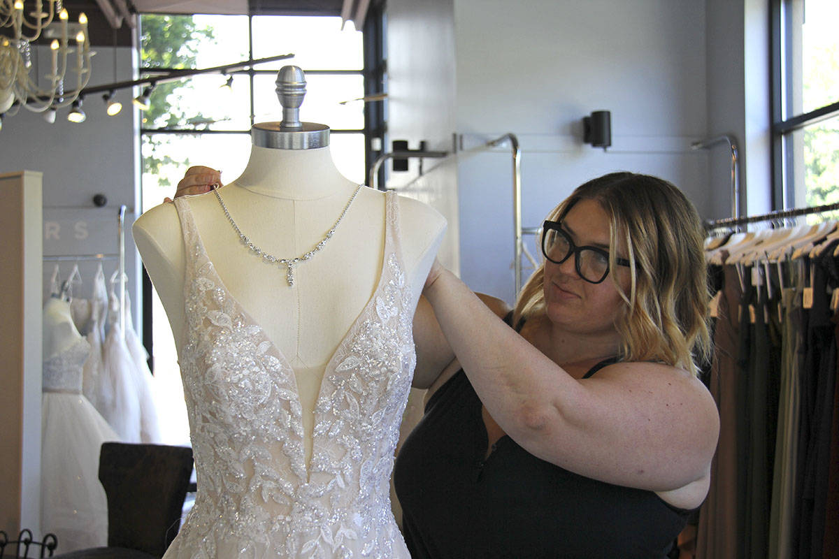 (2:01 p.m.) General manager Rayann Thibault adorns a mannequin with a shimmering necklace at Shades of White Bridal July 15. (Jane Skrypnek/News Staff)