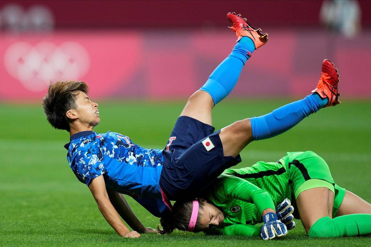 Japan's Mina Tanaka (11) collides with Canada's goalkeeper Stephanie Labbe (1) during a women's soccer match at the 2020 Summer Olympics, Wednesday, July 21, 2021, in Sapporo, Japan. THE CANADIAN PRESS/AP/Silvia Izquierdo