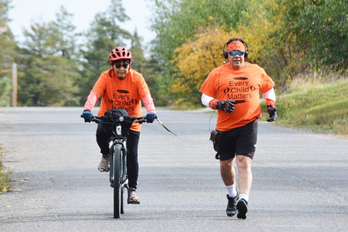 Jackie and James Mattice of Williams Lake First Nation ride and run along Kinglet Drive Tuesday, Sept. 28. The duo runs to honour those who did not survive the residential school system. (Monica Lamb-Yorski/Williams Lake Tribune)