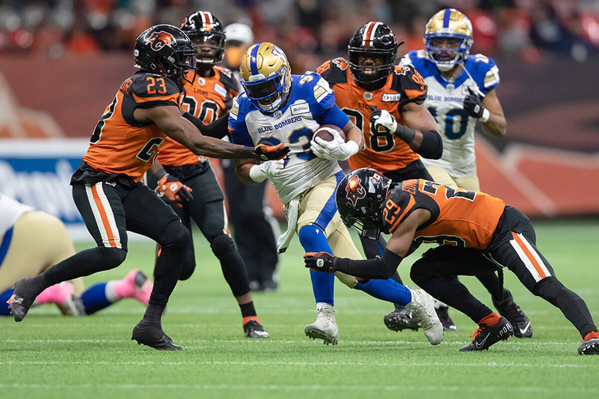 Winnipeg Blue Bombers' Andrew Harris, centre, is tackled by B.C. Lions' Anthony Thompson (23) and Jalon Edwards-Cooper (29) during the first half of a CFL football game in Vancouver, on Friday, October 1, 2021. THE CANADIAN PRESS/Darryl Dyck